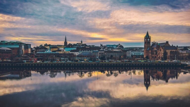 the city of Londonderry reflects on the River Foyle at sunset on a cloudy night
