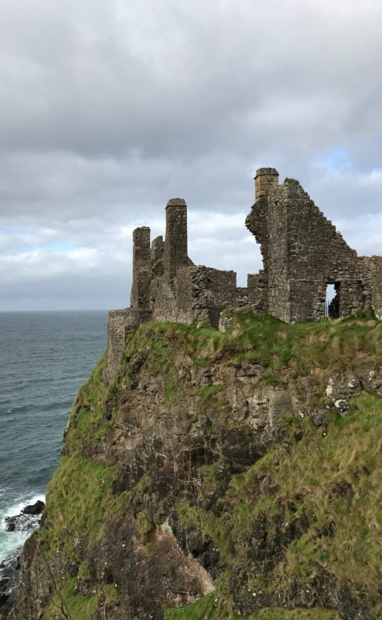 ancient remains of stone and rock on a green rocky cliff where a castle once stood overlooking the water on a cloudy day