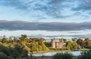 Overlooking a large pond surrounded by green trees and landscape is a castle
